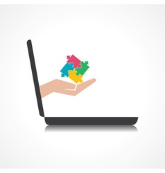 hand holding puzzle piece comes from laptop screen vector image