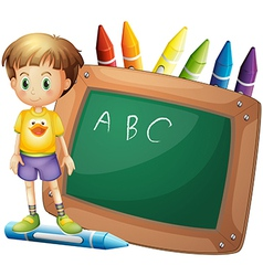 A boy beside a board with crayons at the back vector image