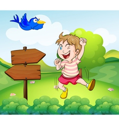 A boy beside a wooden arrow and the blue bird vector image