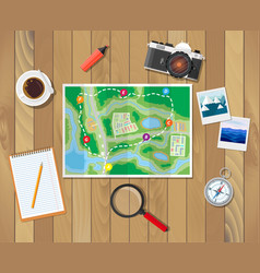 Wooden table with paper map planning trip vector