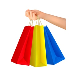 Female hand holding colorful shopping bags vector image