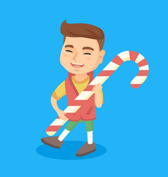 Caucasian little boy holding christmas candy cane vector