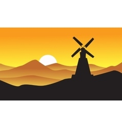 Silhouette of windmill with mountain backgrounds vector