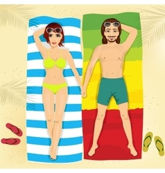 Happy couple in swimsuit lying on towels vector