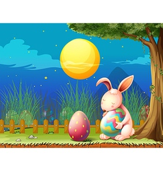 A bunny in the fence with two easter eggs vector