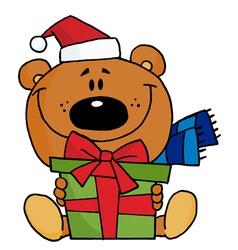 Christmas bear holding a present vector