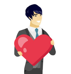 Young asian groom holding a big red heart vector