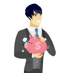 Young asian groom holding a piggy bank vector
