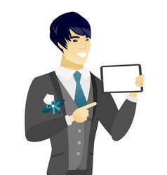 Young asian groom holding tablet computer vector