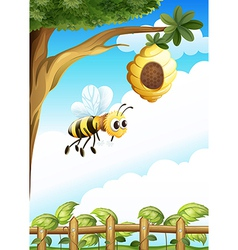 A tree near the fence with a beehive and a bee vector