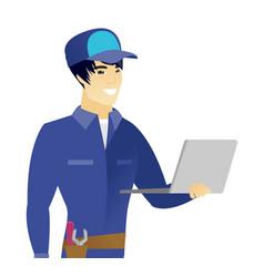 Young asian mechanic using laptop vector
