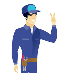 Young asian mechanic showing the victory gesture vector