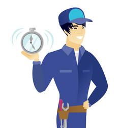 Young asian mechanic holding alarm clock vector