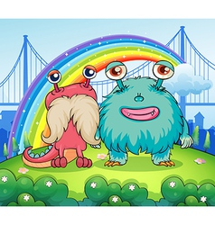 Two weird monsters and a rainbow in the sky vector