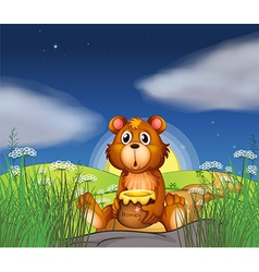 A bear at the hilltop holding a pot of honey vector image