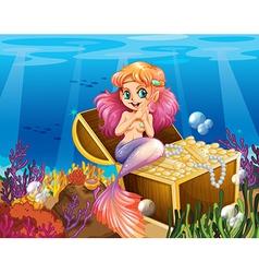 A mermaid under the sea beside the treasures vector image