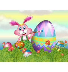 A bunny painting the egg in the garden vector
