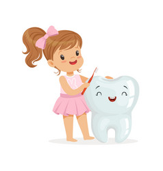 Beautiful girl brushing a big smiling tooth with a vector