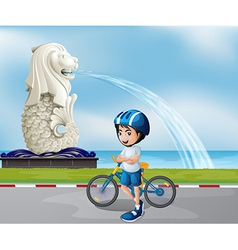 A young biker near the statue of Merlion vector image vector image