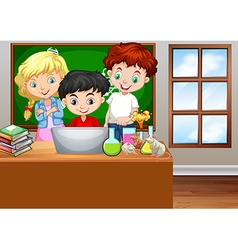 Children looking at computer in classroom vector