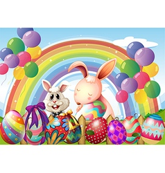 Bunnies and colorful eggs near the rainbow and vector