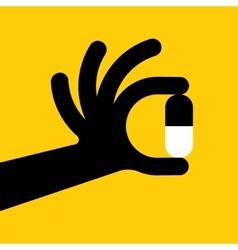 Hand holding a pill vector
