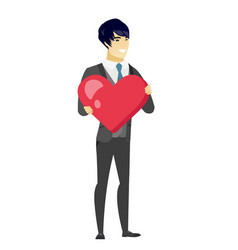 Asian groom holding a big red heart vector