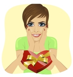Surprised young woman receiving heart shaped box vector
