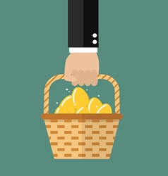 Hand holding wicker basket with golden eggs vector image
