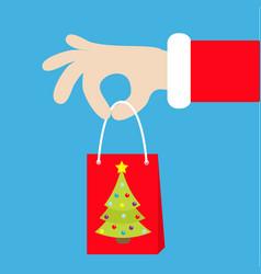 santa claus hand holding gift shopping paper bag vector image vector image