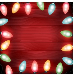 Christmas lights lit on a red wooden background vector
