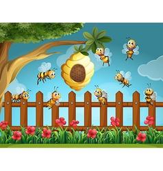 Bees flying around beehive in the garden vector image
