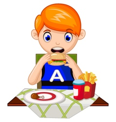 A young boy eating in a restaurant vector