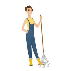 Young caucasian farmer holding gardening rake vector