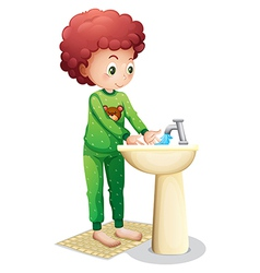 A young boy washing his hands vector image vector image