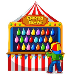 Boy playing darts game at carnival vector