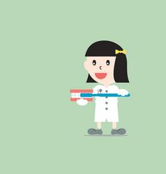 Female dentist demonstrates brushing teeth model vector