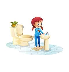 A girl wearing a blue sleepwear washing her hands vector image
