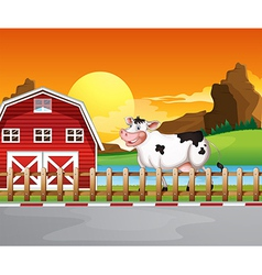 A cow beside the wooden barnhouse vector image vector image