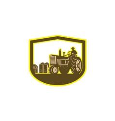 Farmer driving tractor plowing farm shield retro vector