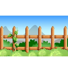 A wooden fence with green plants vector