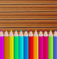 Palette pencils on wooden background vector