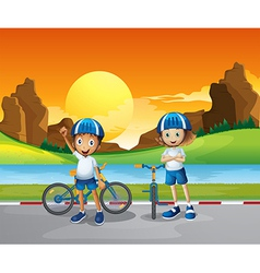 Two kids with their bikes standing at the road vector image