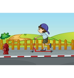 A boy playing with a scooter vector image