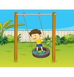 A boy swings on a wheel vector image