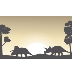 Silhouette of two triceratops on the hill scenery vector