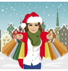 Young woman in santa hat holding shopping bags vector