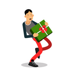 young smiling man carrying a heavy green gift box vector image vector image
