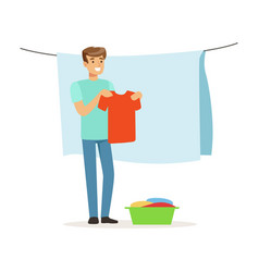 Young smiling man hanging wet clothes out to dry vector