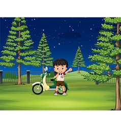 Boy and motorcycle in the park vector